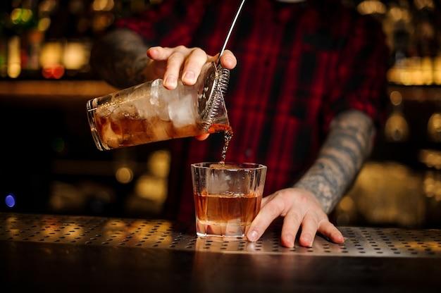 Barman versant un cocktail de la légion étrangère de la tasse à mesurer à travers la passoire à un verre sur le comptoir du bar