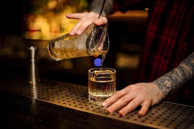 Barman versant un cocktail rusty nail de la tasse à mesurer à travers la passoire à un verre sur le comptoir du bar