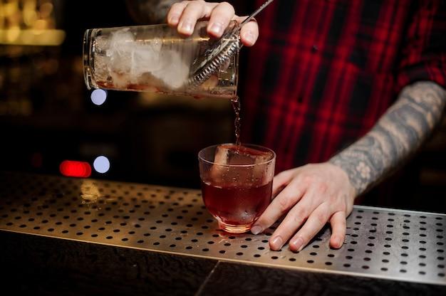 Barman versant un cocktail vieux carré rouge de la tasse à mesurer à un verre sur le comptoir du bar