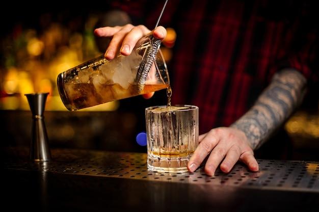 Barman versant un délicieux cocktail rusty nail de la tasse à mesurer à travers la passoire à un verre sur le comptoir du bar