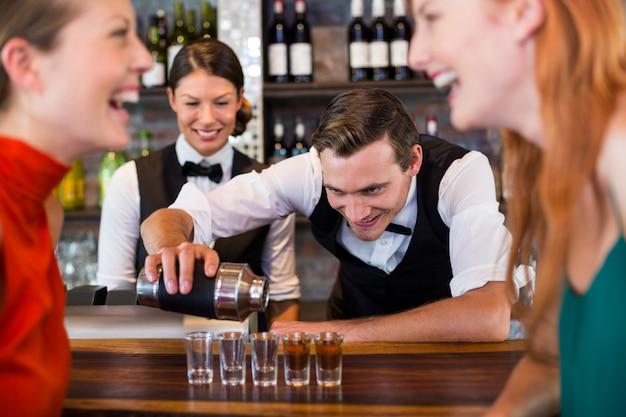 Barman versant de la tequila dans des verres à liqueur