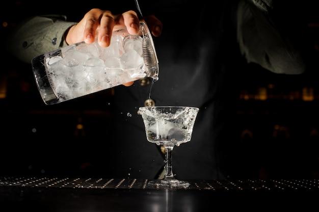 Barman versant un verre d'alcool transparent avec de la glace