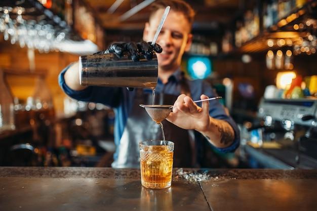 Le barman verse la boisson à travers un tamis dans un verre