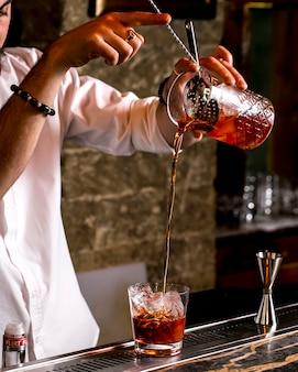Barman verse un cocktail à travers une passoire à cocktail