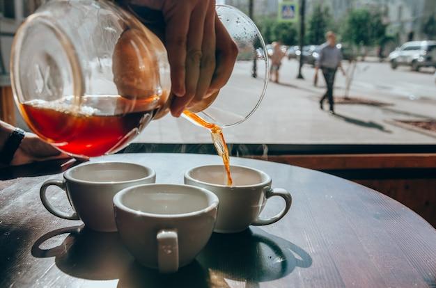 Le barman verse du café dans des tasses