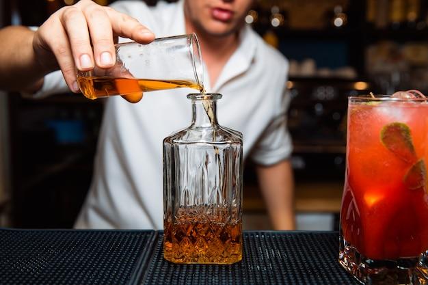Le barman verse du whisky dans une carafe.