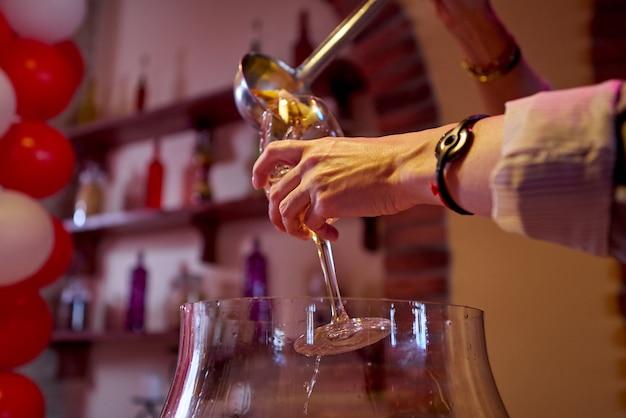 Le barman verse un punch aux fruits dans un verre à vin.