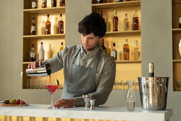 Barman verser un cocktail cosmopolite dans un verre à martini
