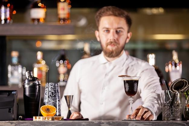 Barmanprésentant un cocktail au café au bar-salon. bonne atmosphère