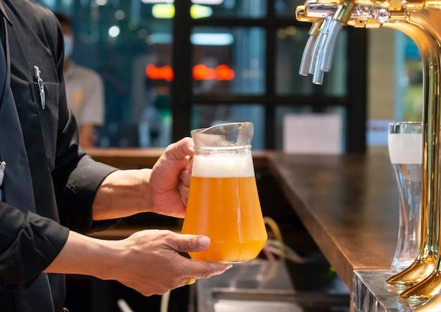 Barmen ou brasseur remplissant le verre avec de la bière