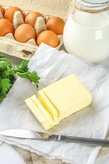 Une barre de beurre est coupée en morceaux sur une planche de bois avec un couteau, du lait, des œufs sur une table blanche