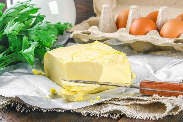 Une barre de beurre est coupée en morceaux sur une planche de bois avec un couteau