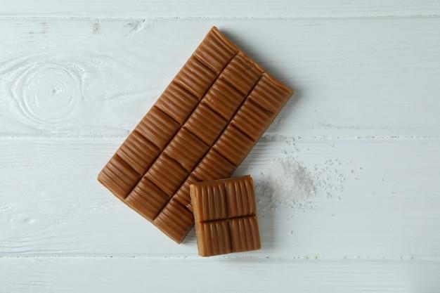 Barre de caramel et sel sur fond de bois blanc