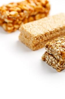 Barre de céréales avec des cacahuètes, du sésame et des graines. vue de dessus trois barres assorties, isoler