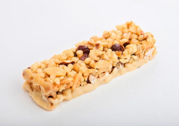 Barre de céréales granola bio fait maison avec des noix et des fruits secs sur blanc.