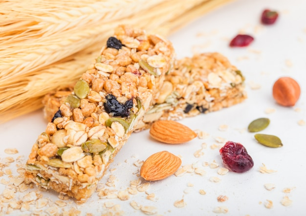 Barre de céréales granola bio maison avec des noix et des fruits secs sur blanc avec de l'avoine et du blé cru.