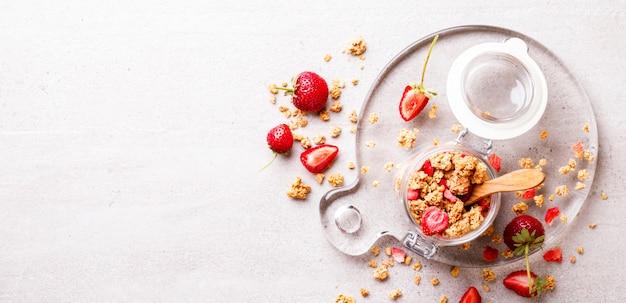 Barre de céréales granola avec fraises dans un bocal en verre. petit déjeuner muesli.