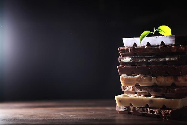 Une barre de chocolat au lait. chocolat au lait maison aux amandes et fraises séchées. morceaux de chocolat au lait. barre de chocolat au lait sans étiquette. ensemble de chocolat avec du thé.