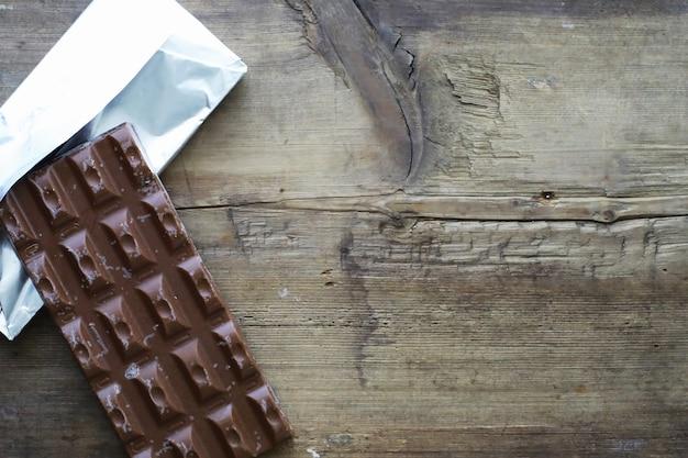 Une barre de chocolat au lait sur la table. chocolat aux noix et saveur de cannelle.