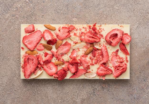 Une barre de chocolat blanc avec des amandes frites et des fraises lyophilisées sur fond clair. vue de dessus, pose à plat.
