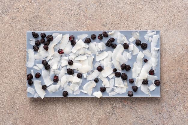 Une barre de chocolat blanc teinté de thé anchan avec des tranches de noix de coco et des bleuets lyophilisés sur fond clair. vue de dessus, pose à plat.