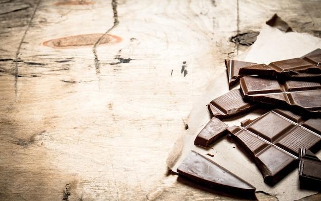 Barre de chocolat cassée sur un fond en bois