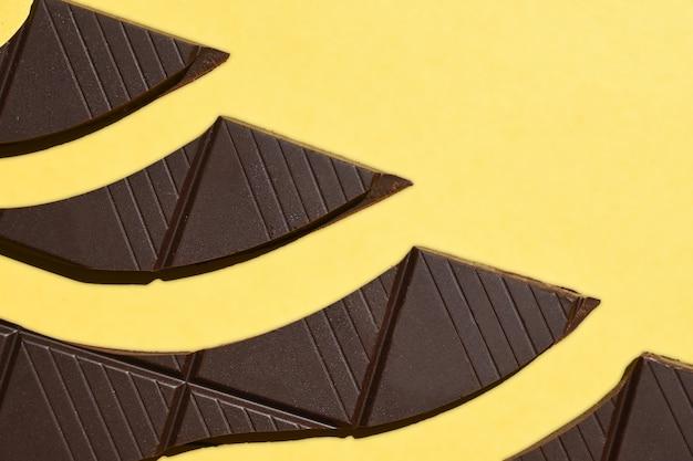 Barre de chocolat cassée en morceaux, sur jaune