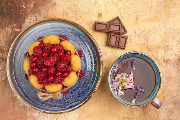 Barre de chocolat gâteau cadeau fraîchement sorti du four et une tasse de thé sur table de couleurs mélangées