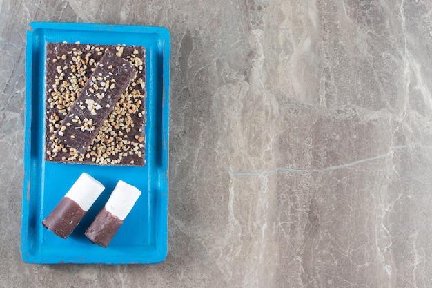 Barre de chocolat gaufre avec noix et bonbons sur plaque de bois sur marbre.