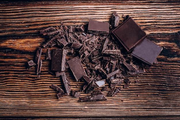 Barre de chocolat hachée sur fond de table en bois.