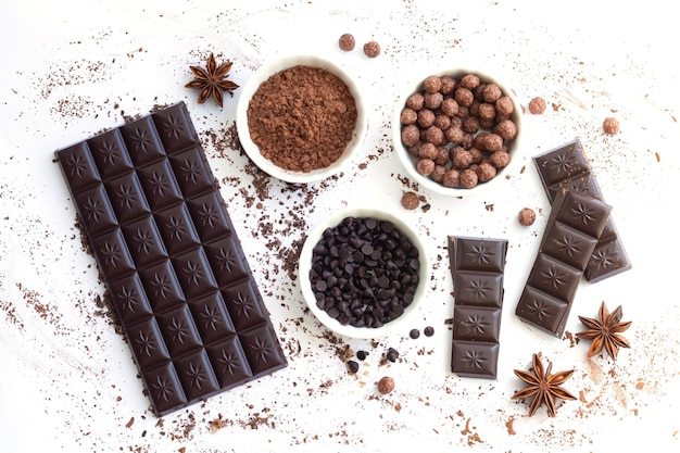 Barre de chocolat et morceaux avec des ingrédients pour la cuisson des aliments sucrés isolés sur la vue de dessus de la surface blanche