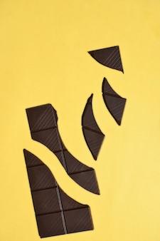 Barre de chocolat noir cassée sur fond jaune