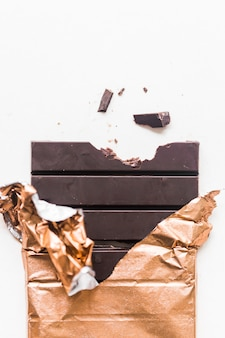 Barre de chocolat noir enveloppé dans du papier doré sur fond blanc