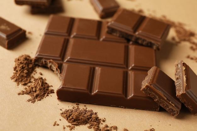 Barre de chocolat savoureuse et poudre sur beige
