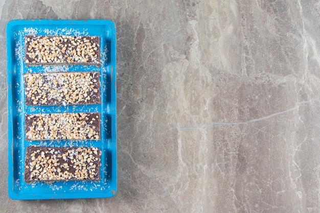 Barre de chocolat en tranches avec noix sur plaque de bois sur marbre.