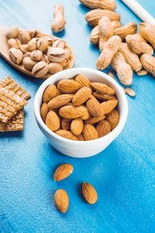 Barre énergétique à base d'amande; cacahuètes; pistache sur fond bleu texturé