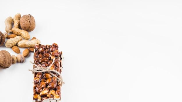 Barre de fruits secs saine énergie attachée avec une ficelle sur fond blanc