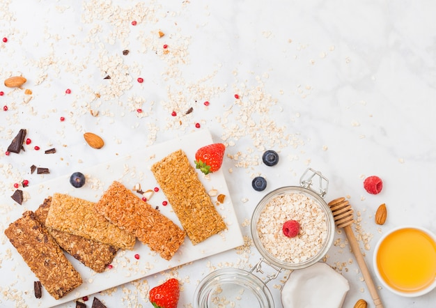 Barre granola de céréales biologiques avec des baies sur une planche en marbre avec une cuillère à miel et un pot d'avoine et de noix de coco sur une table en marbre.