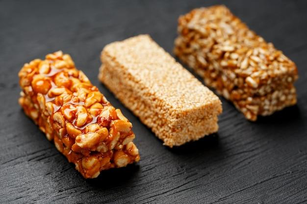 Barre granola de céréales avec des cacahuètes, des graines de sésame et de tournesol sur une planche à découper sur une table en pierre sombre. vue d'en-haut. trois barres assorties