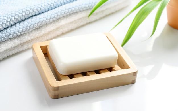 Barre de savon blanc sur porte-savon en bois et serviettes en coton sur table de comptoir blanc dans la salle de bain