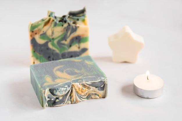 Barre de savon cassée avec une éponge étoile et une bougie illuminée sur fond blanc