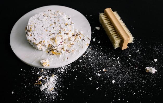 Barre de savon cassée sur un tableau blanc près de la brosse sur une surface noire