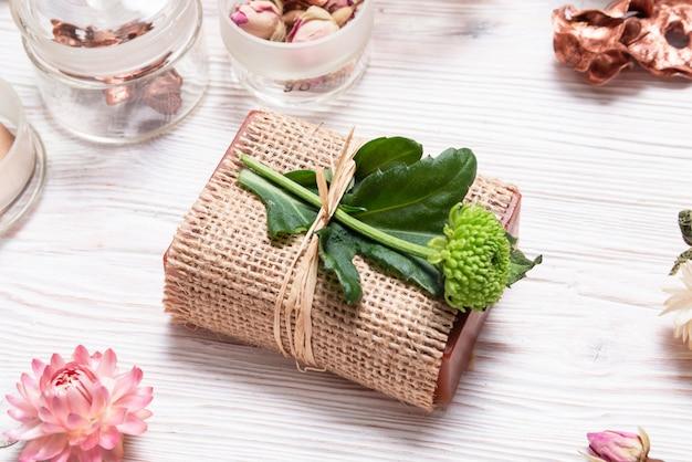Barre de savon fait maison enveloppé dans du tissu de chanvre sur fond de bois