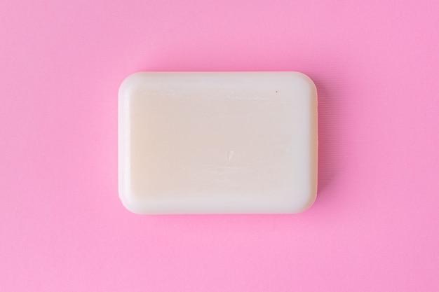 Barre de savon isolée sur fond rose. fermer.