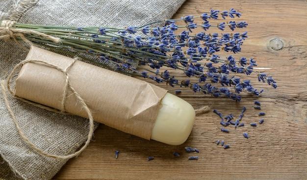 Barre de savon de lavande avec un bouquet de lavande sur un fond en bois avec