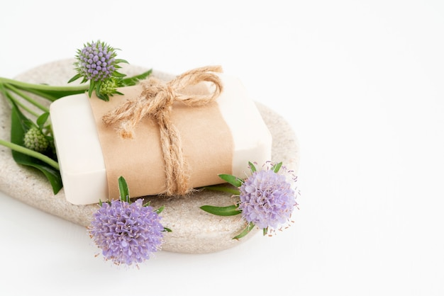 Barre de savon naturel bio sur plateau aux plantes aromatiques