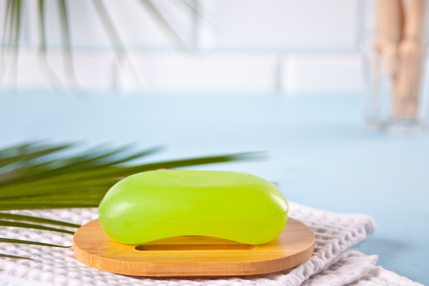 Barre de savon vert sur savon wppden plat et serviette de bain, fond bleu clair. ensemble de bain écologique concept zéro déchet.