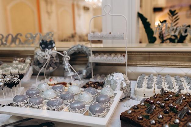 Barre sucrée avec des desserts à la mousse grise, un gâteau au chocolat et des bonbons