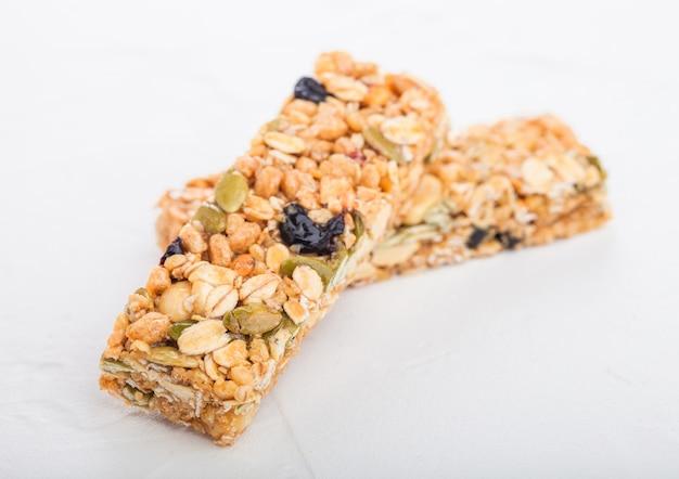 Barres de céréales granola bio faites maison avec des noix et des fruits secs sur blanc.