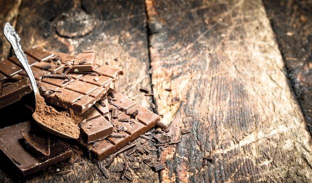 Barres de chocolat au cacao en poudre. sur une table en bois.